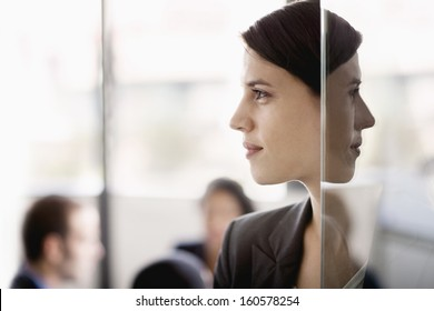 Side profile on businesswoman with coworkers in background
