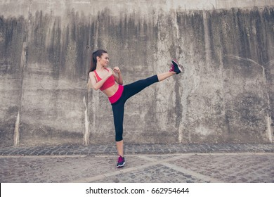 Side profile photo of attractive brunette, kickboxing high kick exercise with her foot outdoors near concrete wall, wearing fashionable pink and black sport wear