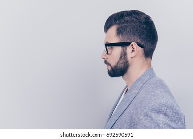Side profile photo of successful young serious handsome brunet bearded businessman in formal outfit and black glasses on pure background