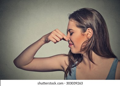Side profile portrait headshot woman pinches nose with fingers looks with disgust away something stinks bad smell situation isolated gray wall background. Human face expression body language reaction