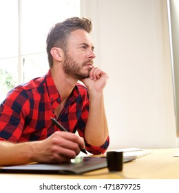 Side profile portrait of man thinking sitting at desk with stylus