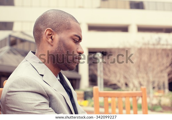 side profile portrait stressed young businessman sitting outside corporate office  looking down. Negative human emotion facial expression feelings.