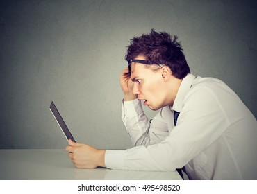 Side profile shocked young man looking at his laptop computer sitting at table