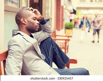 side profile stressed young casual businessman sitting outside corporate office holding head with hands looking down. Negative human emotion facial expression feelings.