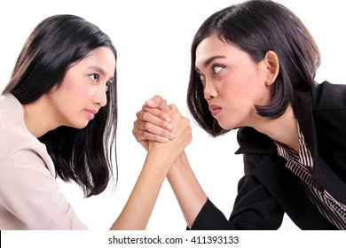 Side profile of two Asian business women doing arm wrestling and staring at each other's eyes, closeup portrait isolated on white background