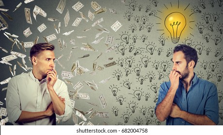 Side profile of two serious businessmen looking at each other one under money rain another with bright ideas
