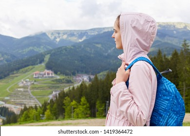 Side profile view of attractive beautiful girl, wearing casual rose jacket and blue rucksack, female backpacking and wandering. Spending spare time in moutains, has active vacation. Traveling concept.