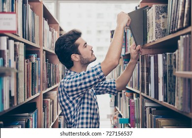 Side profile view of attractive brunet bearded student bookworm, studying in the ancient school library, putting tome on the book shelf, wearing casual checkered shirt, being focused and serious
