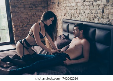Side profile view of attractive long haired model whore take off macho`s trausers in bedroom, so tempting and seductive, dominating, provocate, in nice fashionable  lingerie, with collar on neck