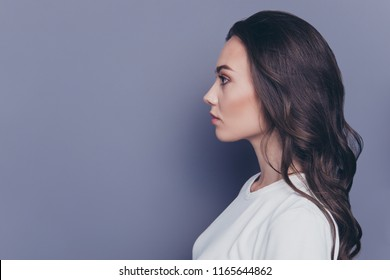 Side profile view of attractive pretty adorable stylish curly-haired girl, isolated over grey background, copy space