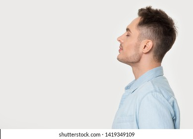 Side profile view man standing on grey background aside empty copy space for your advertisement text. Male in blue shirt closed eyes enjoy fresh air dreaming or positive powerful affirmations concept