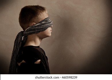Side profile view on serious boy blindfolded with copy space in front him for concept about abduction or hostage taking