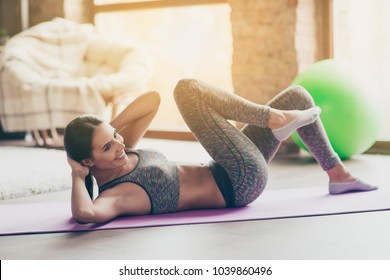 Side profile view photo of cheerful fresh delightful strong enduring slim beautiful attractive dressed in gray tight sportive top and pants  girl doing core crunches on the purple mat at club