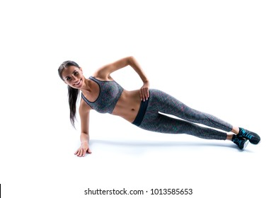 Side profile view photo of happy smiling cheerful sporty flexible young beautiful attractive cute woman clothed in sportive outfit, she is doing plank exercise on one arm, isolated on white background