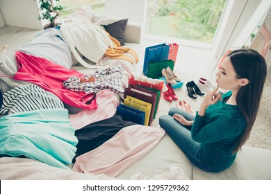 Side profile view photo of pensive pondering lovely beautiful cute woman trying to make choice between large amount of clothes sitting on couch