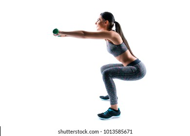 Side profile view portrait of beautiful happy cheerful healthy sporty woman holding dumbbells and squatting, she is improving muscles on her butt, isolated on white background, copyspace