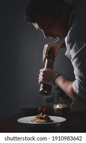 Side profile view young male chef holding pepper shaker peppering spaghetti. Restaurant main course dish, food preparation process concept