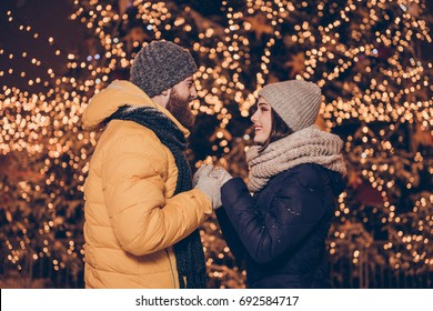 Side profile view of young red bearded man making proposal of marriage on Christmas eve outdoors to his cute brunette lady, she is shocked and amazed, he holds her hands, light around