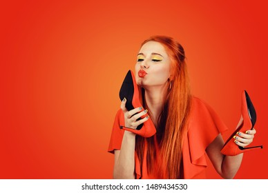 Side profile woman kissing shoe. Women loves high heel shoes concept. Beautiful young happy female model isolated on red wall background