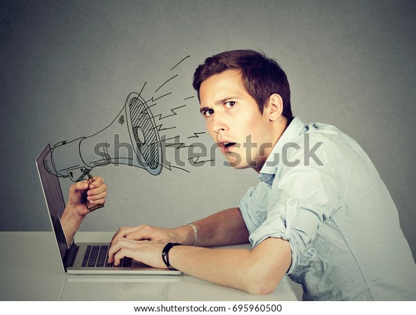 Side profile young anxious man sitting at table using working on a computer with megaphone poking out from a laptop screen