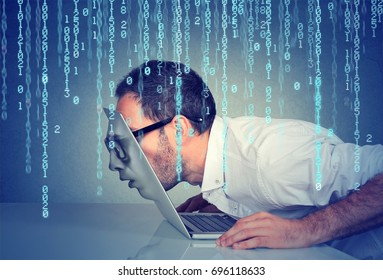 Side profile of a young business man with his face passing through the screen of a laptop on binary code background