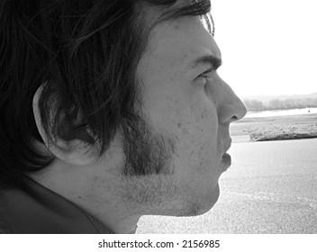 Side profile of young man.  Street in background.