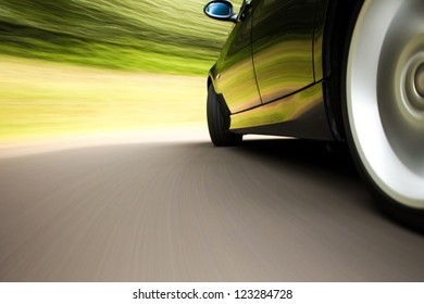 Side rear view of black sport car with heavy blurred motion