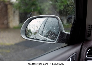 Side rear view mirror on a car. Reflection of rainy day at the car side mirrow.