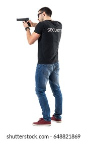 Side rear view of security guard pointing and aiming gun away.  Full body length  portrait isolated on white studio background.