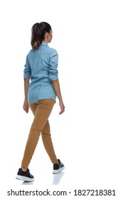 Side rear view of smart casual woman walking and wearing shirt on white studio background