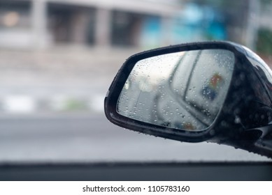 Side rear-view mirror on a modern car with rainy day.