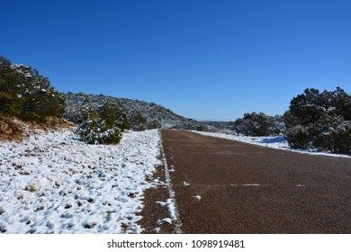 A side road just off of old Route 66 in spring just after a snowfall.  The roadway is clear and the snow covers the rest of the landscape.