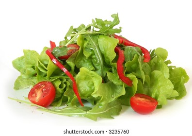 Side salad of butter lettuce and rocket leaves, cherry tomatoes, red capsicum, with cracked pepper and a light dressing.