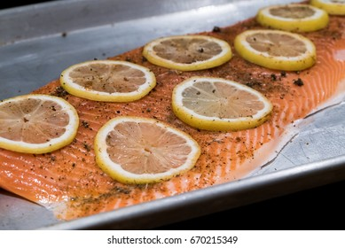 A side of salmon is seasoned and ready to be cooked on a half sheet pan.