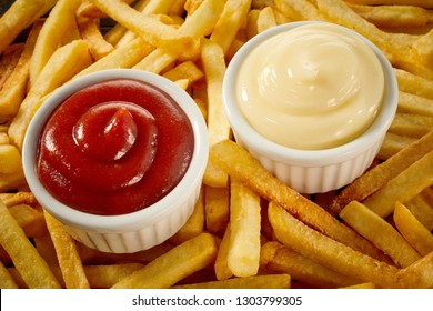 Side servings of tomato sauce or ketchup and mayonnaise on a background of golden crisp fired potato chips, French fries or Pommes Frites