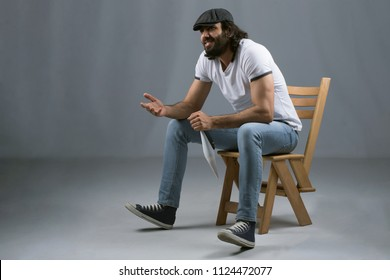 Side shot of a director wearing a casual outfit, sitting on a wooden chair, holding capper board and having a conversation with his friend