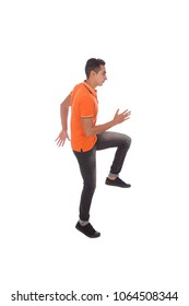 Side shot of a full-length walking man raising leg and hands, isolated on a white background.