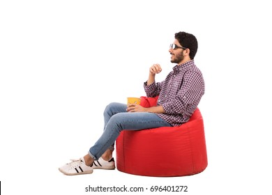 Side shot of handsome happy beard young man with a cinema glasses sitting on a red chair and eating popcorn, guy wearing caro shirt and jeans, isolated on white background