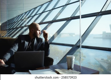 Side shot of handsome successful businessman pensively gazing out of the window thinking about the work plan, attractive young business man looking out of airport hall window, deep in thought