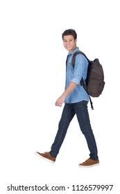 Side shot of a handsome young man wearing a casual outfit, holding a backpack and he is walking going to the college, isolated on white background
