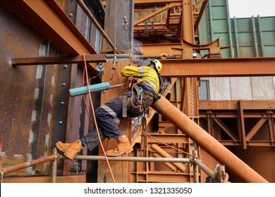 Side shot of industrial isolated rope access welder maintenance abseiler wearing fall safety body harness helmet protective equipment abseiling welding repairing beam structure construction mine site