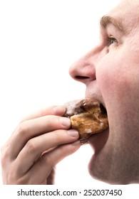 Side shot of man eating donut shot on white