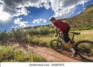 Side shot of mountain biker in red jersey with dramatic sky and