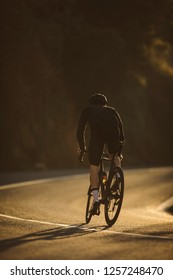 A side shot of a professional slim cyclist riding up a mountain