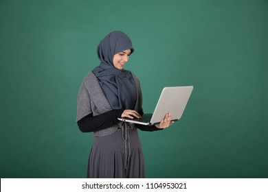 Side shot of a veiled girl standing holding the laptop typing with a smile on a green background.