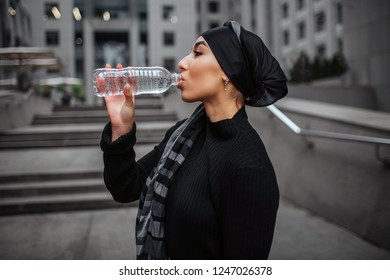 Side shot of young arabian woman drinking water from plastic bottle. She wears black dress and hiijab.