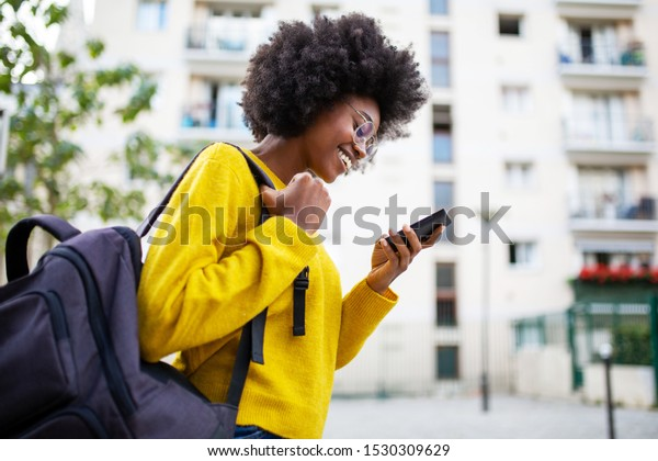 Side of smiling african woman walking in city with bag and phone