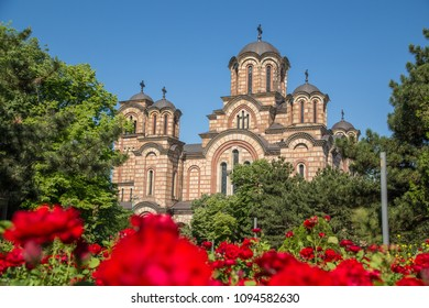 The side of St. Mark's Church, a Serbian Orthodox church in  Belgrade during the day. Roses can be seen in the foreground