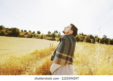 Side of a stand young man enjoying in calm the morning autumn sun in a path of a yellow field with the backlight from the blue sky