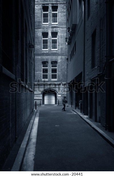 Side street with buildings at sides,  woman at door in distance, blue tone.